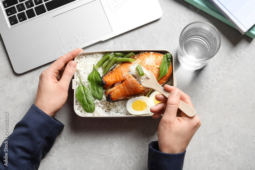 Leinwanddruck Bild Woman eating natural protein food from container at office table, top view