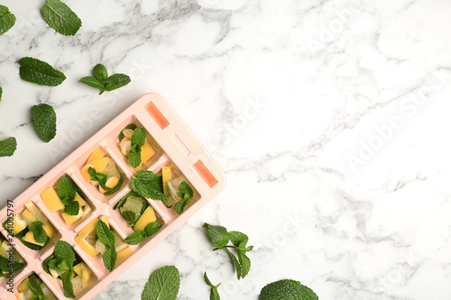 Leinwandbild Motiv Ice cube tray with mint and lemon on marble background, top view. Space for text