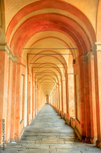 Colonnade of Basilica of San Luca, the longest archway in the world leading to the San Luca Sanctuary of Bologna city in Italy. Architecture background. Vertical shot.
