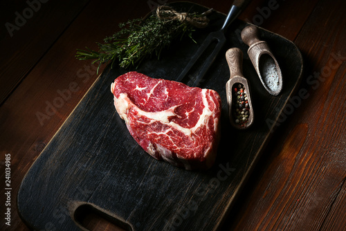 a piece of fresh beef. rib-eye steak. with accompanying ingredients for cooking. concept of delicious dinner. - 241034985