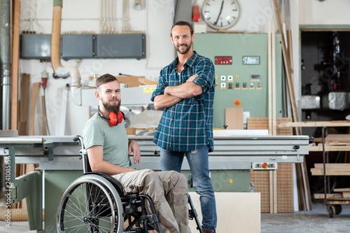 Leinwanddruck Bild worker in wheelchair in a carpenter's workshop with his colleagu
