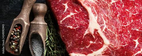 a piece of fresh marbled beef on a wooden background, with spices for cooking steak - 241092943