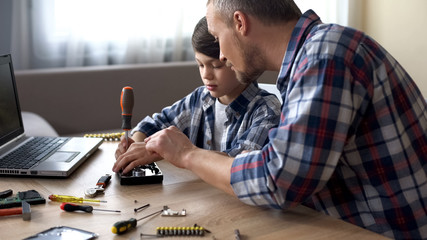 Caring father teaching his little son to repair hard disk drive at home, hobby