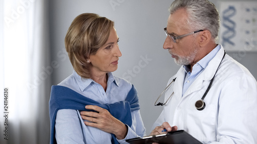 Leinwanddruck Bild Aged physician talking to serious female patient, showing test results, medicine