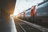 The railroad platform with one empty track and a train consisting of locomotives of red and grey colors on other track, Lisbon, Portugal, shallow depth of field