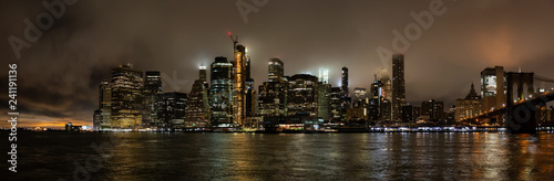 obraz PCV Panoramic view of the Downtown Manhattan and Brooklyn Bridge during a foggy night. Taken in New York, NY, United States.