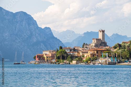 Leinwanddruck Bild Idyllic coast in Italy: Blue water and a cute village at lago di garda, Malcesine