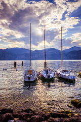 Sailing boats at an italian lake, sunset, mountains and clouds