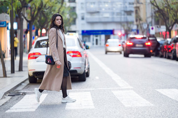 Pretty young woman holding coffee and looking sideways while crossing the street.