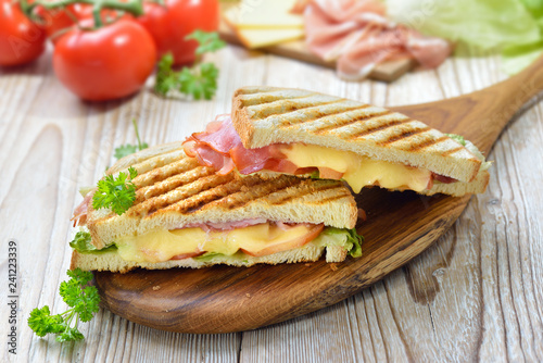 Getoastetes und im Kontaktgrill gepresstes italienisches Panini mit Schinken, Käse , Tomaten und Salat  - Pressed and toasted panini with ham, cheese, tomatoes and lettuce - 241223339