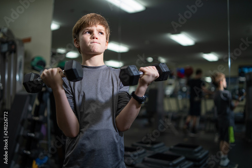 Little boy working out with weights in gym child fitness  - 241226772
