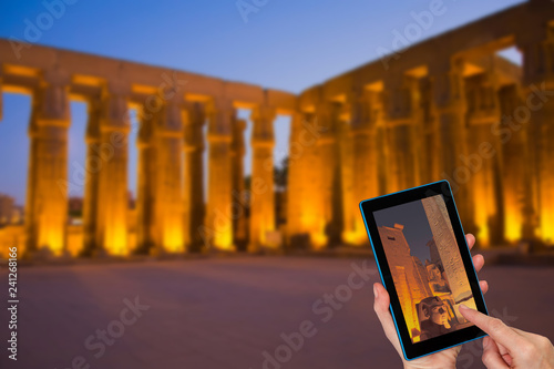 Hands of tourist touching tablet screen with a focused Ramese statue and entrance to the Luxor Temple. Intentionally blurred image of Luxor Temple is in the background. (Egypt )