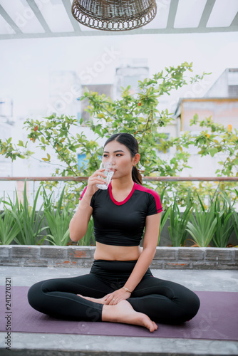 Young asian woman drinking water from glass after exercise yoga and meditation