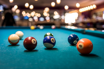Colorful billiard balls on playing table, dispersed