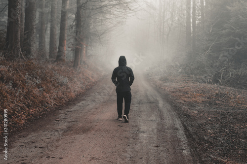 single boy walking through a forest landscape in a country footpath