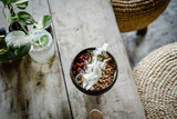 Green smoothie bowl with goji, coconut chips and granola topping on light wooden table. Overhead, copy space. Food photography, healthy eating  concept - 241294166