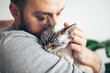 Leinwandbild Motiv Cat and man, portrait of happy cat with close eyes and young beard man. Handsome young man is hugging and cuddling his cute color point Devon Rex kitten. Domestic pets concept