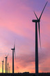 Vertical format of silhouettes of wind turbines on a farm in Iowa on a sunset sky background