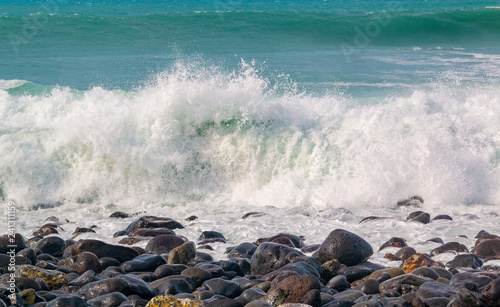 Wave splash on volcanic stones close-up - 241311159