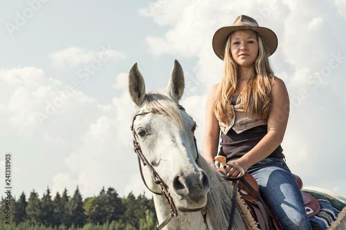 Leinwandbild Motiv Junge Frau mit Cowboyhut  reitet auf Araberstute