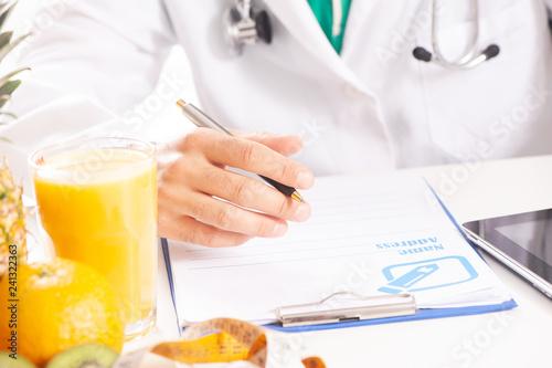 Foto Murales Nutritionist doctor writing diet plan on table.