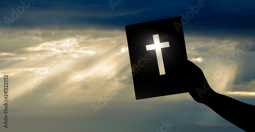 Silhouette, Hand hält Bibel vor lichtdurchflutetem Himmel