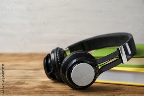Leinwanddruck Bild Modern headphones with hardcover books on wooden table, closeup. Space for text