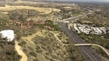 Aerial Drone Footage Slow Pan Up with Freeway and Construction site in Distance - 241325332