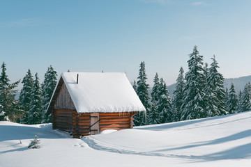 Fantastic winter landscape with wooden house in snowy mountains. Christmas holiday concept. Carpathians mountain, Ukraine, Europe