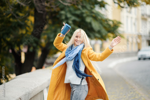 Stylish happy young blond woman in bright yellow coat holds coffee to go. Walking on the street. Portrait of a young cheerful woman at work break. Lifestyle concept  - 241333373