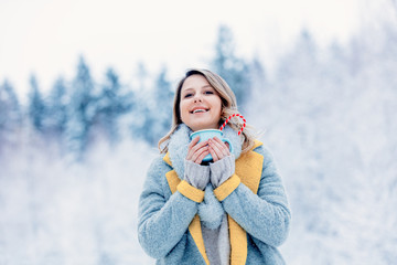 Beautiful girl in gray coat with cup of hot drink in a snow forest. Christmas of Valentine Day season time © Masson