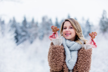 Beautiful girl in coat with cookie in a snow forest. Christmas of Valentine Day season time © Masson
