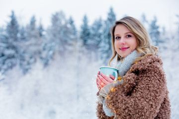 Beautiful girl in coat with cup of hot drink in a snow forest. Christmas of Valentine Day season time © Masson