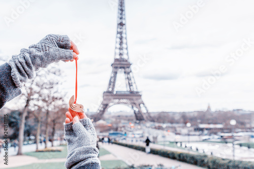 Woman holding little ceramic bird on the Eiffel Tower background. Paris, France