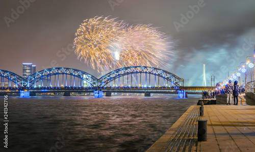 obraz lub plakat New Year's evening with colorful fireworks in Riga over river Daugava. Railroad bridge with colorful reflections from fireworks.