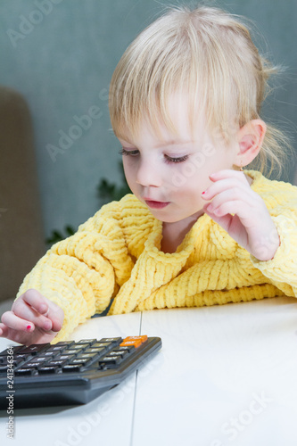 small child enthusiastically counts on a calculator - 241346364