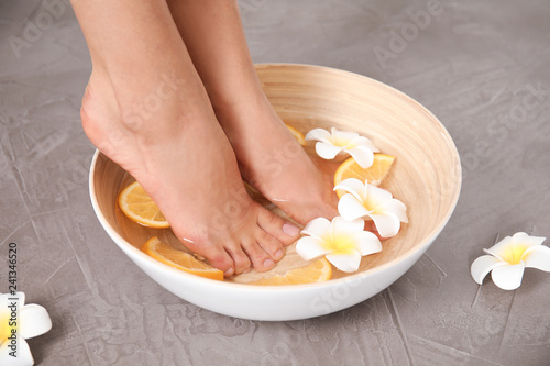 Leinwanddruck Bild Woman soaking her feet in bowl with water, orange slices and flowers on grey background, closeup. Spa treatment