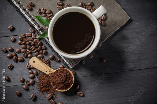 Hot coffee cup with coffee beans and the ground powder of coffee on the wooden table - 241354783