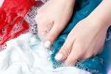 Female hands washing multicolored clothes in basin, top view - 241369347