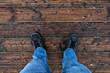 Person in Jeans steht auf Holzboden