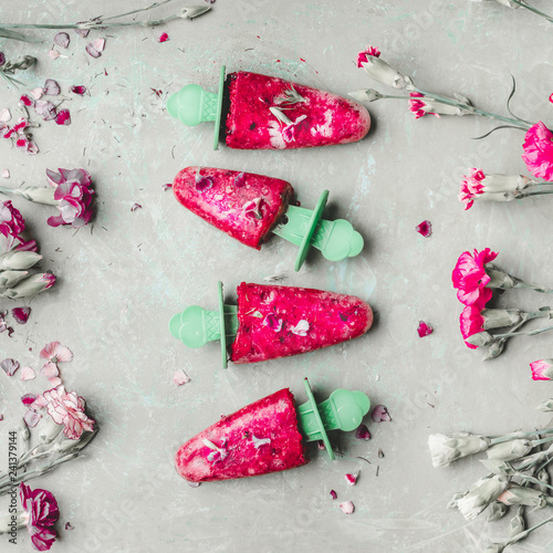Fruits and berries popsicle ice . Homemade ice cream on light green kitchen table background, top view. Healthy summer desserts. Frozen juices on sticks. Vegan ice