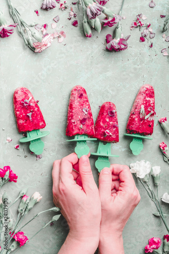 Female hands holding fruits popsicle ice. Homemade red ice cream on light green kitchen table background, top view. Healthy summer desserts. Frozen juices on sticks. Vegan ice. Summer food