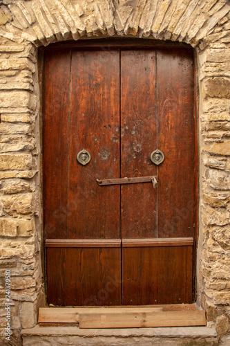 Medieval wooden door, adorned with stone