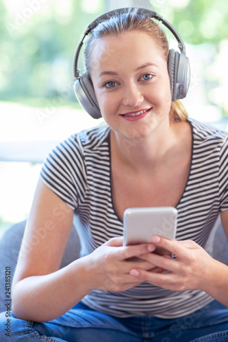 Portrait Of Woman At Home Streaming Music From Mobile Phone To Wireless Headphones - 241385120