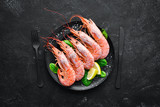 Great Royal Shrimps in a plate. Tiger prawns. Top view. Free space for your text. On the old background. - 241386342