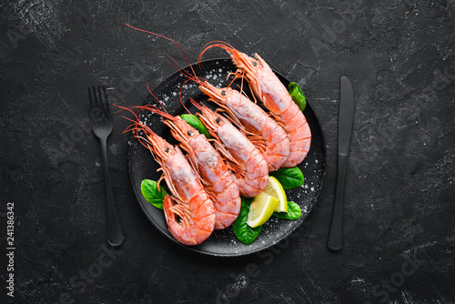 Great Royal Shrimps in a plate. Tiger prawns. Top view. Free space for your text. On the old background.