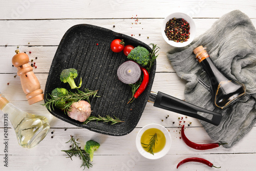 Grill pan for cooking. On a white wooden background. Top view. Free copy space.