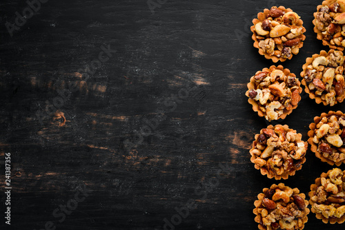 obraz lub plakat Cookies with caramelized nuts. On a wooden background. Top view. Free copy space.