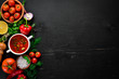 Vegetable background. Fresh tomatoes, paprika, onions and parsley on the table. Top view. On a black background. Free space for text.