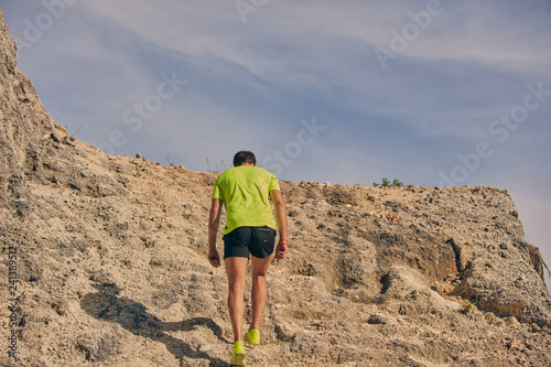 Sportsman climbing the rock / hill for hard exercise. - 241389512